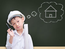 Little builder in helmet thinking. Little Asian  builder in helmet thinking in front of chalkboard Stock Images