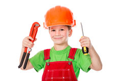 Little builder in helmet with wrench and screwdriver Stock Photo