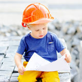 Little builder reading construction drawing Stock Photos