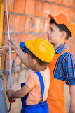 Little builders. In hardhats with measuring tape working outdoors royalty free stock photos