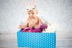 Little bunny in the box. Cute baby girl with bunny ears - studio shot Royalty Free Stock Photography