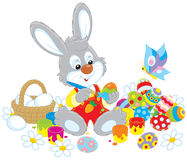 Little Bunny paints Easter eggs Stock Photo
