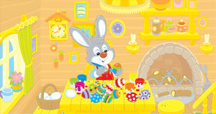 Little Bunny paints Easter eggs Royalty Free Stock Photography