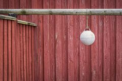 A little buoy in front of a typival scandinavian building. A little buoy or marine fender in front of a typival scandinavian building with falu red. Was seen in royalty free stock image