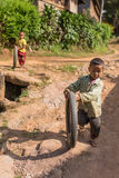 Little burmese boy playing with the bike tyre in the village near Hsipaw, Myanmar Stock Photography