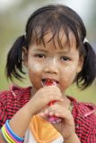 Little Burmese girl eating candy Stock Images