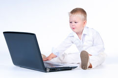 Little business boy in  solid white suit sitting at notebook. Stock Photos