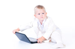 Little business boy in  solid white suit sitting at notebook. Stock Photo
