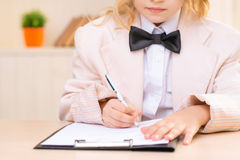 Little business girl is filling out a paper Royalty Free Stock Photo