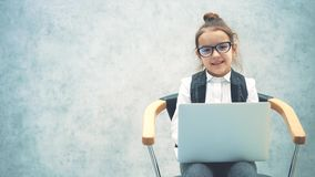 Little business girl smiling at the gray background. During this time, the laptop is kept. Sitting on the chair and
