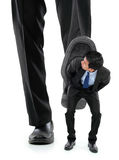 Little business man being crushed by the feet Royalty Free Stock Photography