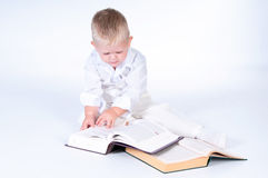 Little business man in solid white suit reads books Royalty Free Stock Image