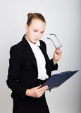 Little business woman in glasses thought a new idea. Studio portrait of child girl in business style holding documents. Royalty Free Stock Image