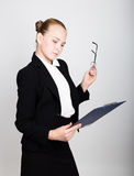 Little business woman in glasses thought a new idea. Studio portrait of child girl in business style holding documents. Royalty Free Stock Images