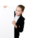 Little business woman standing behind and leaning on a white blank billboard or placard, expresses different Stock Photo