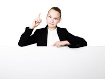 Little business woman standing behind and leaning on a white blank billboard or placard, expresses different. forefinger Royalty Free Stock Images