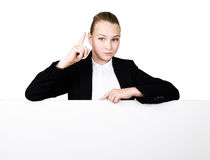 Little business woman standing behind and leaning on a white blank billboard or placard, expresses different. forefinger Royalty Free Stock Image