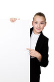 Little business woman standing behind and leaning on a white blank billboard or placard, expresses different. shows a Royalty Free Stock Images