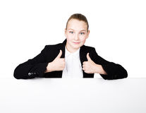 Little business woman standing behind and leaning on a white blank billboard or placard, expresses different. thumb up Royalty Free Stock Image