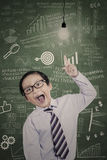 Little businessman has idea in class. Little businessman pointing at lit bulb in classroom Stock Photo