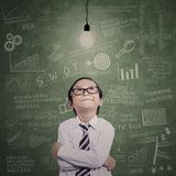 Little businessman looking at lit bulb in class. Little businessman looking at lit bulb with drawn formula on the board Royalty Free Stock Photo