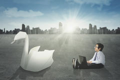 Little businessman and origami swan Stock Images