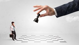 Little businessman playing chess with a big hand concept stock photos