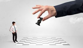 Little businessman playing chess with a big hand concept royalty free stock image