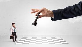Little businessman playing chess with a big hand concept royalty free stock images