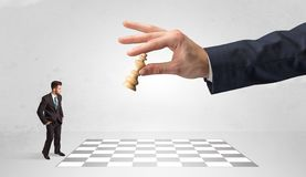 Little businessman playing chess with a big hand concept royalty free stock photos
