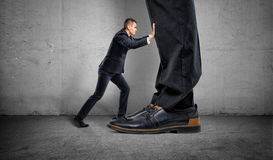Little businessman is pushing a big boss`s huge feet on gray background Royalty Free Stock Images