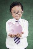 Little businessman showing piggybank 1 Stock Photography