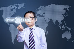 Little businessman with a start button Royalty Free Stock Images
