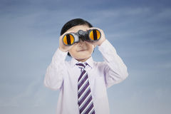 Little businessman using binoculars outdoor Stock Photography