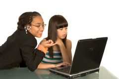 Little businesswomen. Two girls and a laptop, isolated Royalty Free Stock Photo