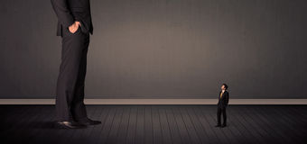 Little bussinesman in front of a giant boss legs concept. On background Royalty Free Stock Image