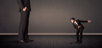 Little bussinesman in front of a giant boss legs concept Royalty Free Stock Photos