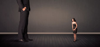 Little bussineswoman in front of a giant boss legs concept Royalty Free Stock Image