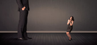Little bussineswoman in front of a giant boss legs concept Royalty Free Stock Images