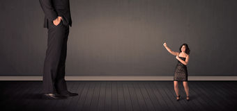 Little bussineswoman in front of a giant boss legs concept Royalty Free Stock Photography