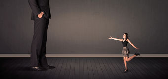 Little bussineswoman in front of a giant boss legs concept Royalty Free Stock Photos