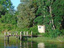Little Cabin By The Water. Wooded shoreline on the river stock photography