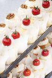 Little cakes decorated with cherry tomatoes and walnuts Royalty Free Stock Photos