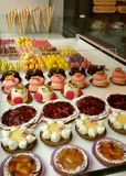 Little cakes. Multicoloured individual little cakes and macaroons in patisserie shop window Royalty Free Stock Photography