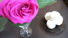 Little cakes and rose on wooden table on Valentine's Day. Love the concept of romance. Little cakes and rose on wooden table on Valentine's Day. Love the stock video footage