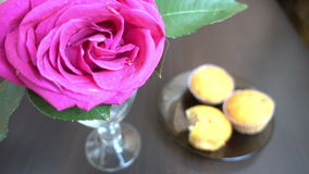 Little cakes and rose on wooden table on Valentine's Day. Love the concept of romance. stock footage