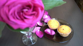 Little cakes and rose on wooden table on Valentine's Day. Love the concept of romance. Hd stock video footage