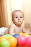 Little calm baby laying on the floor. With colorful balls Stock Photo