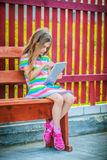 Little calm girl playing on Tablet PC Stock Photography
