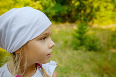 Little calm girl in white scarf in profile Stock Photos